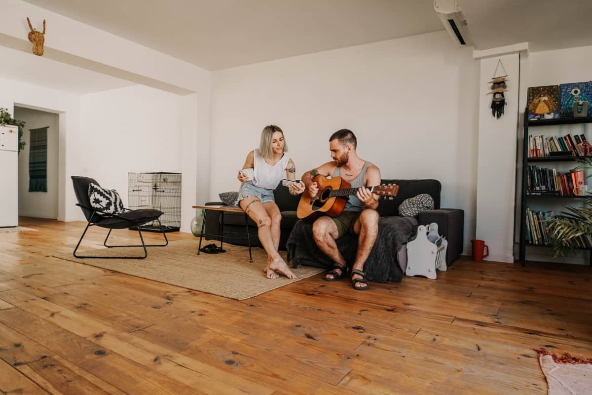 How To Learn Guitar In Home - Man And Woman On Couch Playing Guitar