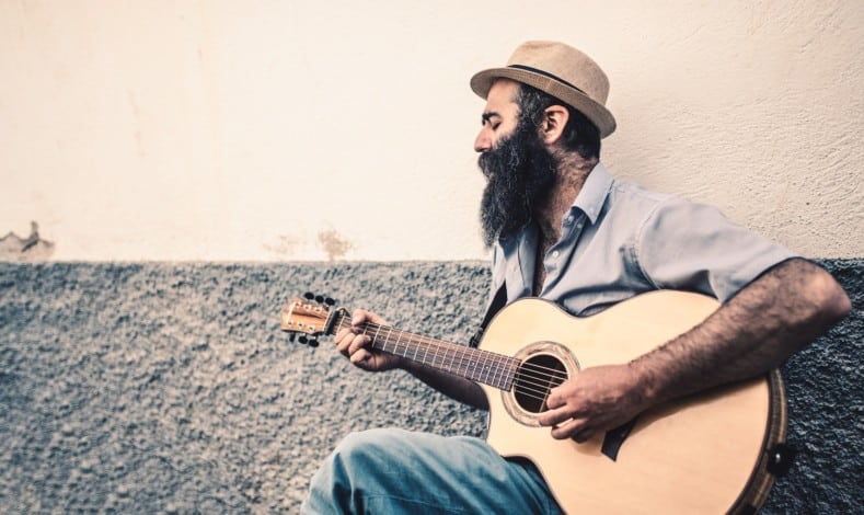 can you learn guitar at any age - adult playing acoustic guitar