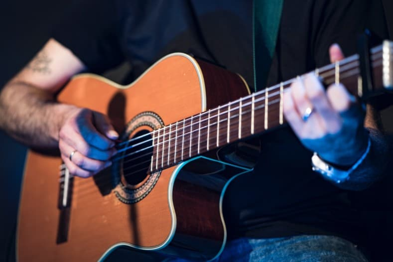 easy to learn acoustic guitar songs - man playing acoustic guitar