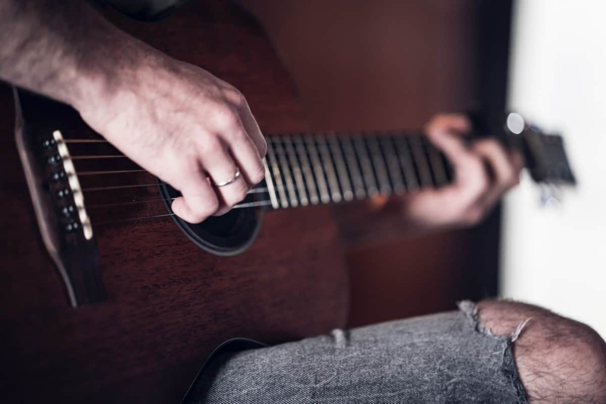 how long does it take to learn acoustic guitar - man playing acoustic guitar