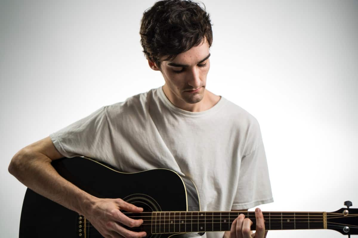 how to use a guitar tuner - man playing acoustic guitar
