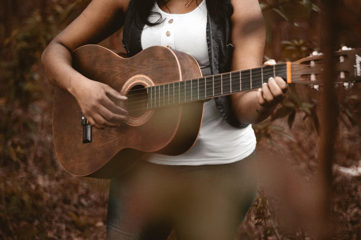 learn fingerpicking guitar - woman playing acoustic guitar