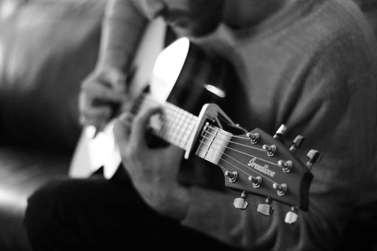 learn how to strum an acoustic guitar - man playing acoustic guitar
