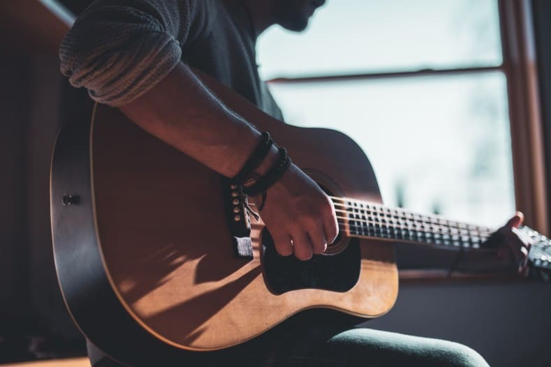 tips for learning guitar - man playing acoustic guitar