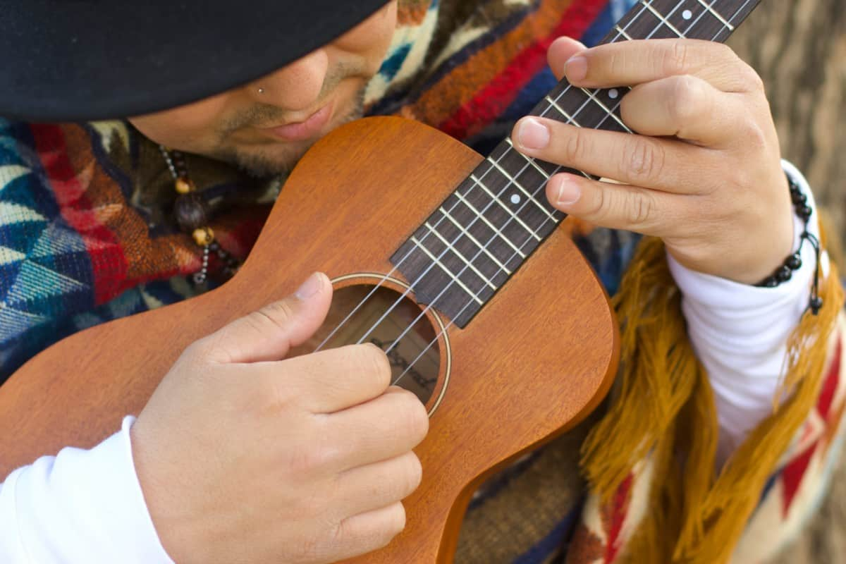 which is easier to learn guitar or ukulele - man playing ukulele