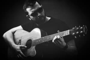 why learn guitar scales - man playing acoustic guitar