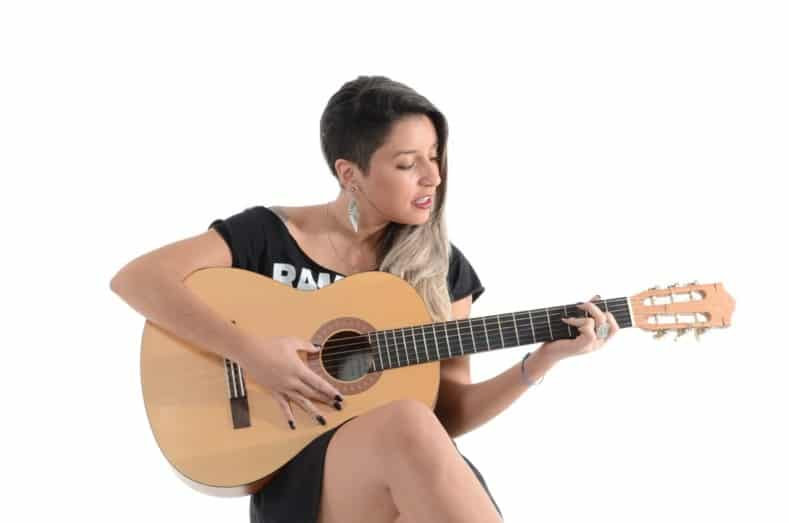 woman is singing and playing guitar at the same time